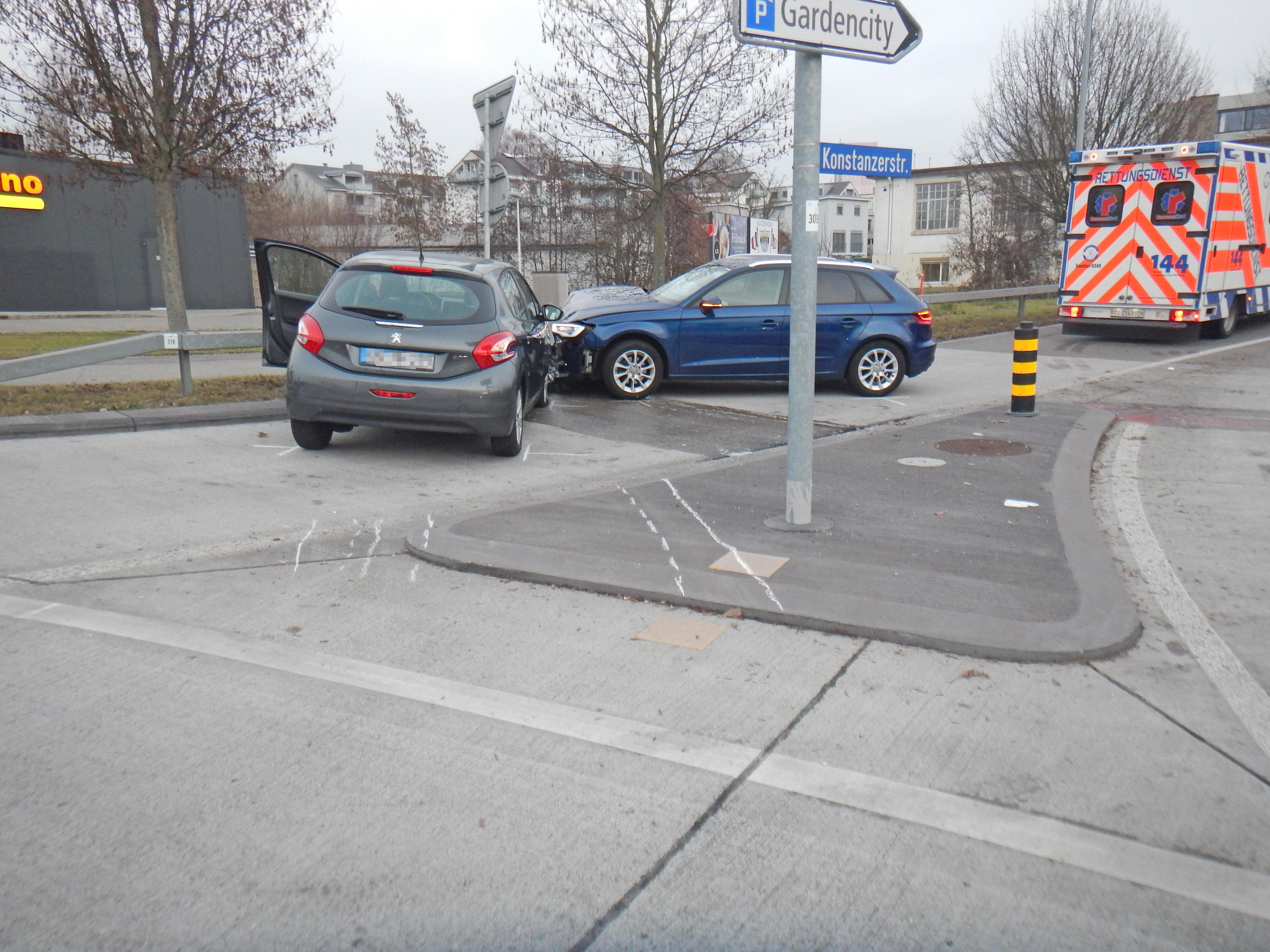 Zwei frontal kollidierte Fahrzeuge im Kreisel, im Hintergrund der Rettungsdienst.